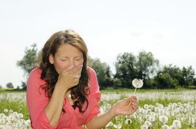 Frau niest auf einer Blumenwiese